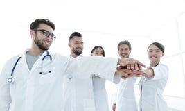 Médecins et infirmières dans une équipe médicale empilant des mains Images libres de droits