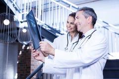 Médecins examinant un rapport de x sur l'escalier Photographie stock