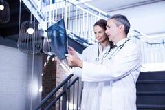 Médecins examinant un rapport de x sur l'escalier Photos libres de droits