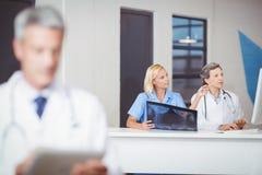 Médecins féminins avec le rayon X tout en travaillant au bureau d'ordinateur image libre de droits