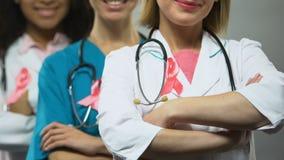Médecins féminins avec les rubans roses posant pour la caméra, conscience de cancer du sein banque de vidéos