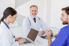 Médecins généralistes habiles discutant la santé des personnes image libre de droits