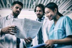 Médecins heureux et infirmière ayant la discussion au-dessus des rapports médicaux image libre de droits