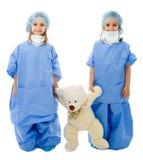 Médecins jumeaux d'enfants avec l'ours de nounours image stock