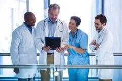 Médecins masculins et infirmière ayant la discussion au-dessus du presse-papiers dans le couloir photographie stock