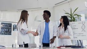 Médecins multi-ethniques d'équipe en manteaux blancs et verres médicaux se serrant la main entre eux après consultation dans clips vidéos