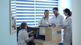 Médecins passant en revue les dossiers patients à la réception d'hôpital images libres de droits