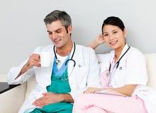 Médecins positifs détendant et buvant du café image stock
