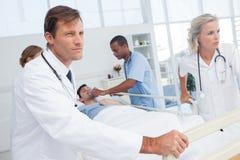 Médecins poussant le lit d'un patient Photo stock