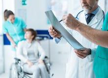 Médecins professionnels examinant le rayon X patient du ` s photographie stock