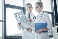 Médecins qualifiés attentifs donnant sur le balayage et le sourire de rayon X Photographie stock