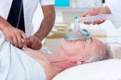 Médecins réanimant un patient aîné Photographie stock