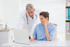 Médecins regardant l'ordinateur portable photo stock