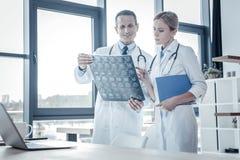 Médecins sûrs qualifiés tenant et examinant le balayage de rayon X Photos stock