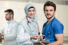 Médecins saoudiens travaillant avec un comprimé Photo stock