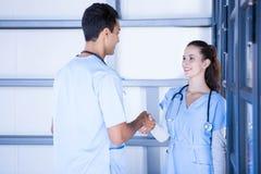 Médecins se serrant la main dans le couloir photographie stock