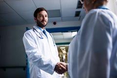 Médecins se serrant la main dans le couloir Images libres de droits