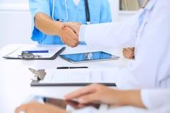 Médecins se serrant la main finissant entre eux la réunion médicale Photo libre de droits