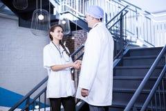 Médecins se serrant la main sur l'escalier photos libres de droits