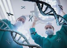 Médecins se tenant avec des brins d'ADN 3D Photographie stock