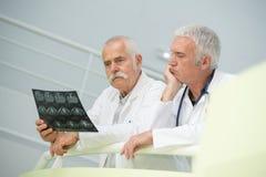 Médecins supérieurs semblant perplexes au-dessus du rayon X Photo stock