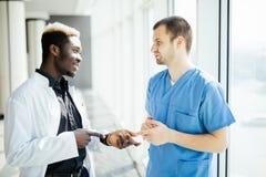 Médecins Talking As They Walk du métis deux par l'hôpital moderne photographie stock