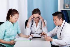 Médecins travaillant à côté de la table images stock