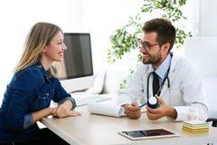 Médicament de prescription de jeune docteur masculin beau pour le patient dans le bureau médical à l'hôpital photographie stock