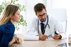 Médicament de prescription de jeune docteur masculin beau pour le patient dedans photo libre de droits