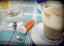 Médicament pendant le petit déjeuner, capsules à côté d'un verre de l'eau, image conceptuelle photos libres de droits