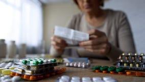 Médicament se trouvant sur la table, prescription en difficulté de lecture de dame âgée derrière, plan rapproché photographie stock