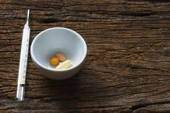 Médicaments dans une tasse et un thermomètre Image stock