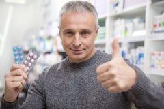 Médicaments mûrs d'achats d'homme à la pharmacie photo libre de droits