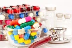 Médicaments oraux, fioles stériles et stéthoscope sur W image stock