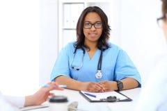 Médico afroamericano de sexo femenino con el colega en hospital Fotografía de archivo