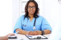 Médico afroamericano de sexo femenino con el colega en hospital Imagen de archivo