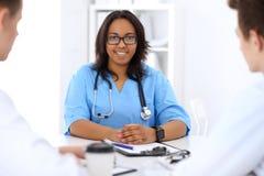 Médico afroamericano de sexo femenino con el colega en hospital Imágenes de archivo libres de regalías