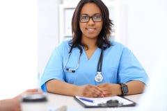 Médico afroamericano de sexo femenino con el colega en hospital Foto de archivo