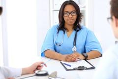 Médico afroamericano de sexo femenino con el colega en hospital Imagen de archivo libre de regalías
