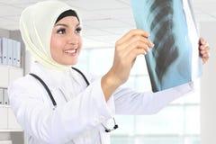 Médico asiático de sorriso que olha o raio X imagem de stock royalty free