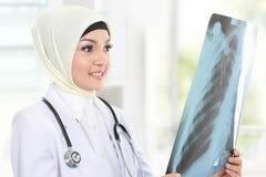 Médico asiático de sorriso que olha o raio X imagens de stock