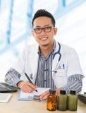 Médico asiático que trabalha em sua mesa imagem de stock royalty free