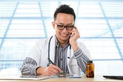 Médico asiático que trabalha na mesa fotos de stock