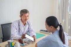 M?dico asi?tico superior que olha o paciente f?mea com sorriso ao apontar na tela da tabuleta digital imagem de stock