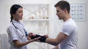 Médico bueno que aplica al paciente masculino sonriente del apoyo de la muñeca del titán, rehabilitación almacen de metraje de vídeo