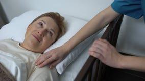Médico bueno que frota ligeramente el hombro femenino viejo, paciente mayor que miente en el lecho de enfermo, rehabilitación metrajes