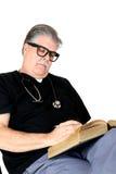 Médico com estetoscópio que estuda e que lê um livro Foto de Stock Royalty Free
