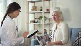Médico com tabuleta que visita a mulher envelhecida em sua casa filme