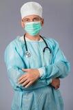 Médico con el estetoscopio y la mascarilla que se colocan con los brazos foto de archivo libre de regalías