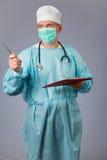 Médico con el estetoscopio y la mascarilla que sostienen un cuaderno imagen de archivo